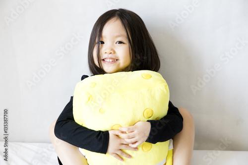 Asian girl holding yellow plush toy Wallpaper Mural