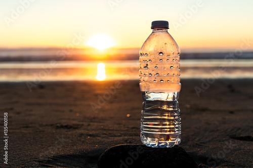 Fotografia, Obraz  Plastic bottle of water on the beach at sunset , sunrise time