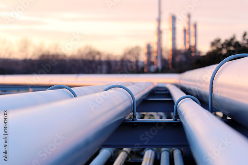 Fototapeta steel long pipes in crude oil factory during sunset obraz