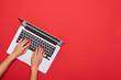 Leinwanddruck Bild - Woman skinny hands working on a silver laptop on a red desktop a