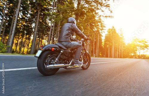 Tuinposter Fiets Back view of motorcycle driver on road