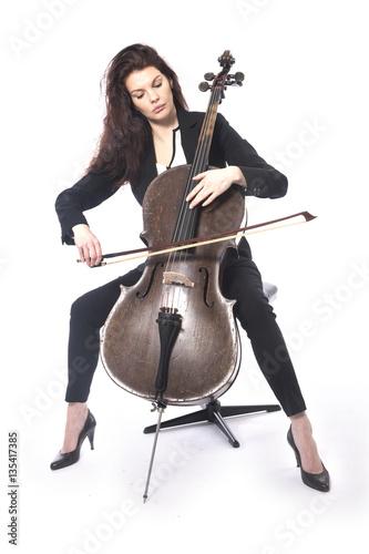 Fotografija beautiful brunette woman plays the cello in studio against white