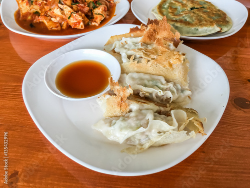 Dim sum : Gyoza, it made wrappers and meat in white plate on wood table Canvas Print
