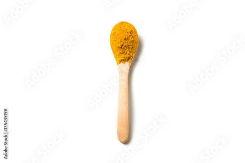 Fototapeta Turmeric powder in a wooden spoon isolated over white background obraz