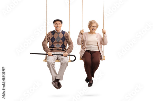 Fototapety, obrazy: Elderly man and an elderly woman sitting on swings