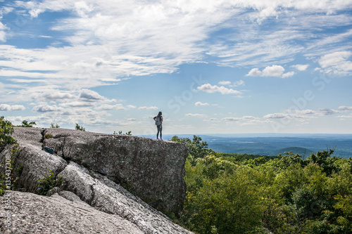 Photo  Young woman hiker overlooking landscape on cliff