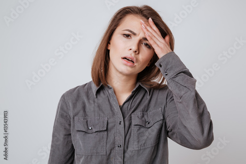 Fotografia  Sick young woman with headache touching her head.
