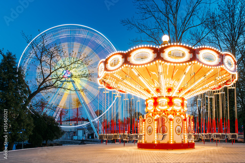 Photo sur Toile Attraction parc Illuminated Attraction Ferris Wheel And Carousel Merry-go-round
