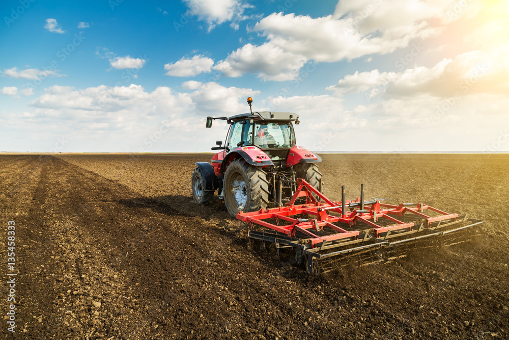 Fototapety, obrazy: Farmer in tractor preparing land with seedbed cultivator as part of pre seeding activities in early spring season of agricultural works at farmlands.