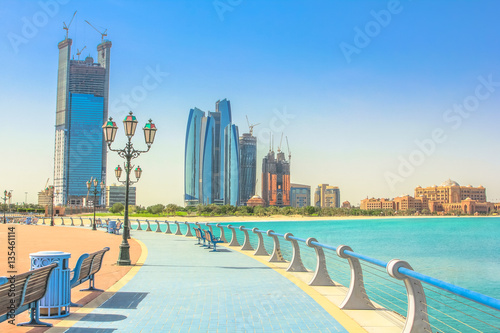 Poster Abou Dabi Dhabi skyline from cycle paths of Corniche. Abu Dhabi, United Arab Emirates, Middle East. Modern skyscrapers and landmark on background. Summer holidays concept.
