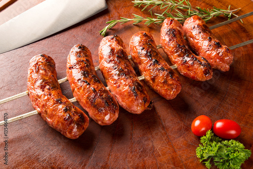 Fotomural Sausages on the barbecue spit on wooden background