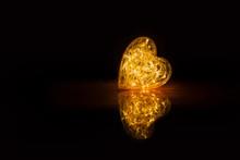 Warm Glowing Orange Heart With Reflection On Dark Black Background
