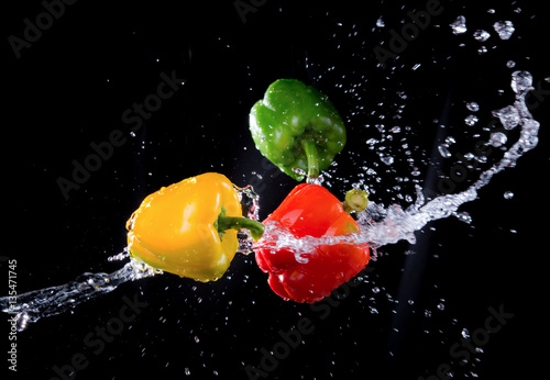 Poster Légumes frais Bell peppers peppers with splash isolated on black background.