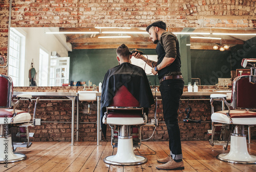 Fotografija  Hairstylist serving client at barber shop