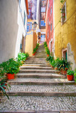 Fototapeta Na drzwi - Narrow european street with cobblestone steps and old houses, Portugal