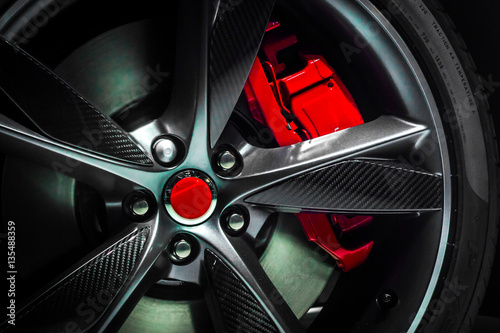 Fotografía  Closeup of a beautiful large Alloy wheel of luxury car with painted brake callip