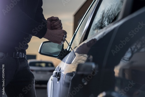 Fotografía  Auto thief in black balaclava trying to break into car
