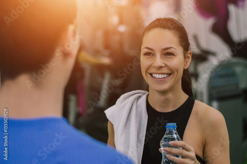 Portrait of beautiful girl at gym, talking with personal trainer