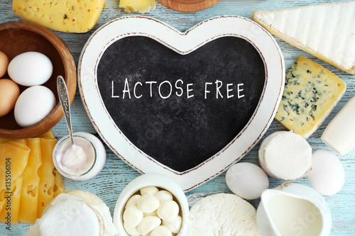 Allergic food concept. Dairy products and heart shaped board with text LACTOSE FREE on table