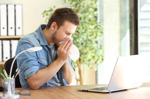 Fotografia  Ill entrepreneur sneezing at office
