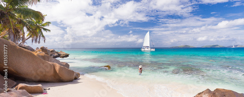 Fotografie, Obraz  Woman wearing long floral summer dress and beach hat on Anse Patates beach on La Digue Island, Seychelles