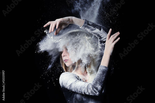Photo  Little cute girl dancing with white powder on black background