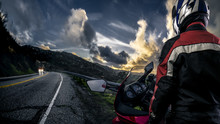 Male Motorcyclist Wearing Protective Leather Racing Suit With A Red Bike Or Motorcycle On An Open Road.  The Vehicle Is Cropped To Become Generic Non Branded. The Image Depicts Travel And Adventure.