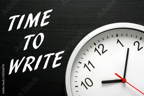 Fotografiet  The words Time To Write in white text on a blackboard next to a clock as a remin