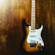 Vintage Sunburst Color Guitar With Old Wood Surface In Background.
