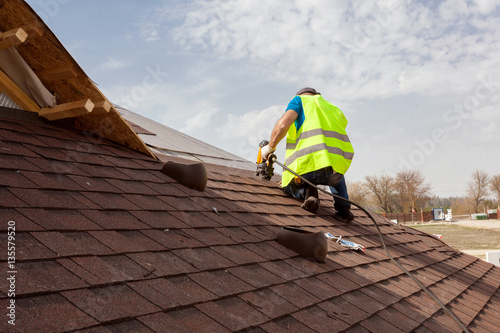Valokuvatapetti Construction worker putting the asphalt roofing (shingles) with nail gun on a la