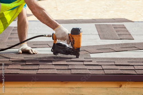 Obraz Construction worker putting the asphalt roofing (shingles) with nail gun on a new frame house - fototapety do salonu
