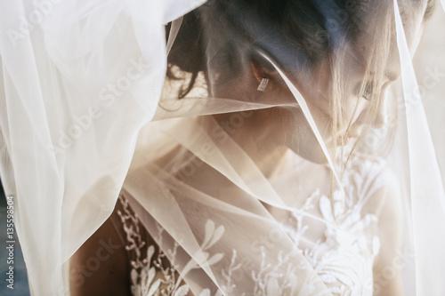 Light veil hides tender young bride Fototapeta