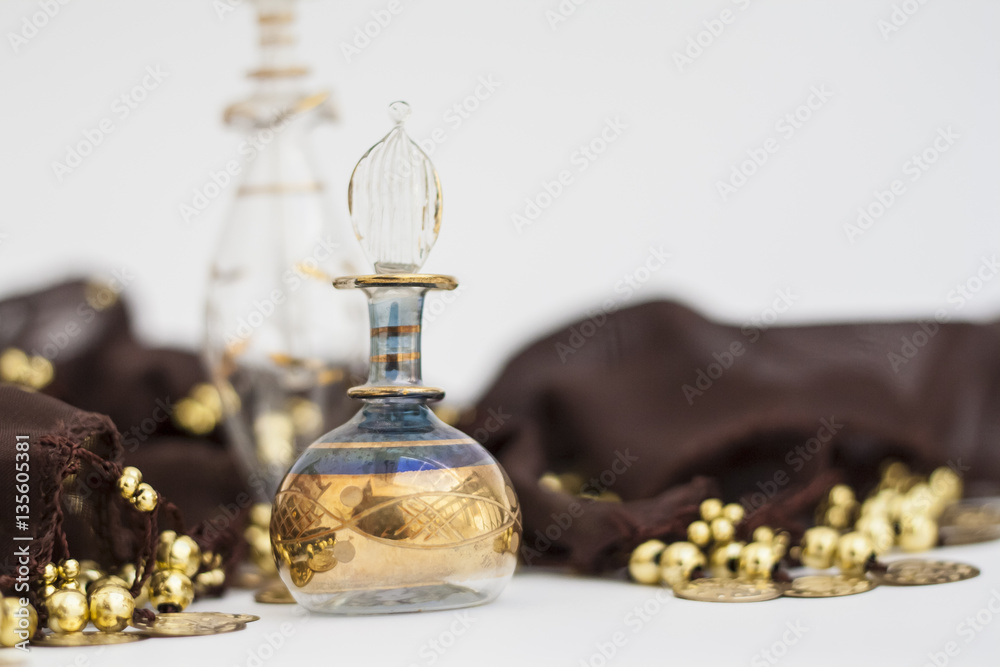 Fototapety, obrazy: Arabian parfum bottles and brown belly dance belt with golden coin. Blurred photography, selective focus on glass decorations.