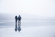 Couple in the mist walking on the lake ice in winter afternoon. Peaceful atmosphere. Foggy air.