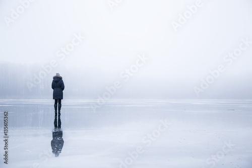 Plakat Kobieta w mgły odprowadzeniu na jeziornym lodzie w zimy popołudniu. Spokojna atmosfera. Mgliste powietrze.