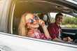 Happy young woman in the car with her husband is happy with glasses