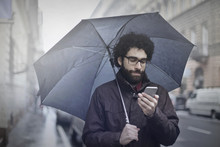 Man With Umbrella And Phone