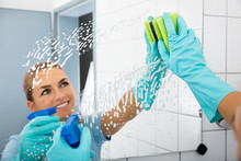 Smiling Woman Cleaning The Mirror Of The Bathroom