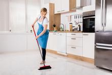 Housemaid Sweeping Floor In Kitchen