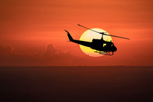 Flying Helicopter Silhouettes On Sunset Background.  The Patrol Helicopter Flying In The Twilight Sky.
