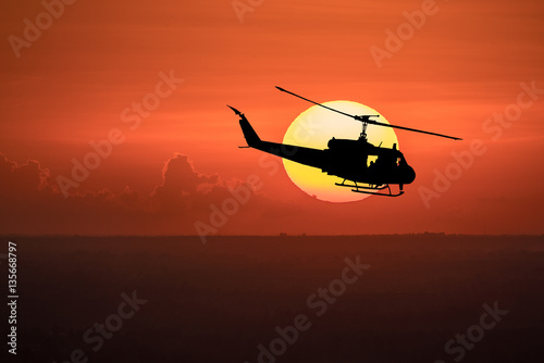 Fotobehang Helicopter Flying helicopter silhouettes on sunset background. The patrol helicopter flying in the twilight sky.