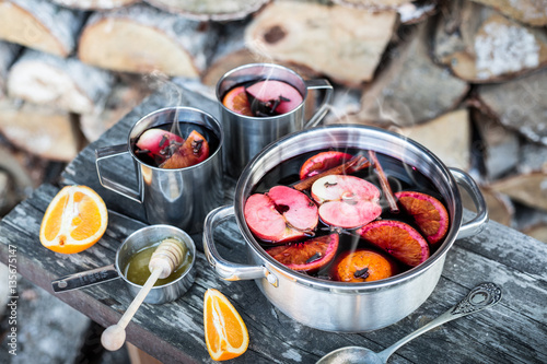 Hot mulled wine outdoor in a pot - winter or autumn picnic