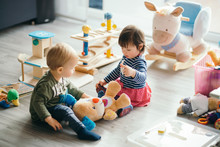 Little Girl And Boy Playing With Toys By The Home