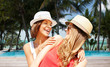 happy young women in hats on summer beach