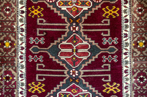 Fotografering  Edges and central part with folk eastern ornament on woolen carpet in burgundy b