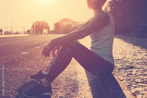 Fototapety, obrazy: Sporty and fit woman sitting on the street, resting after nice workout. Urban sport. Vintage colors