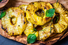Grilled Pineapple Slices On Olive Wooden Board. Top View