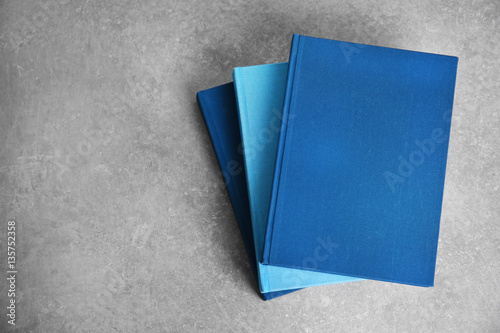 Fotografering  New hardcover books on gray background