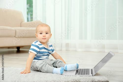 In de dag Retro Cute baby boy with laptop on carpet