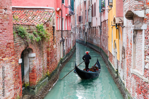 Tuinposter Gondolas Venetian gondolier punting gondola through green canal waters of Venice Italy